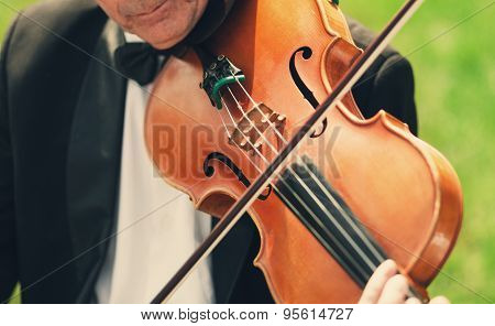 Musician With Bow Tie Plays Violin Outdoors