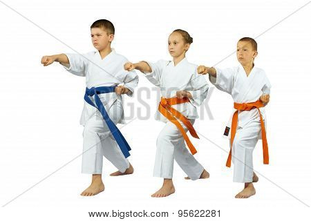 Sportsmen in the rack of karate are beating blow gyaku-tsuki