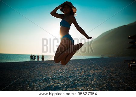Woman jumping in the air on tropical beach,having fun and celebrating summer,beutiful playful woman