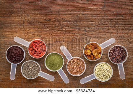 superfood abstract (wheatgrass, acai berry, goji berry, flax seed,chia seed,goldenberry,hemp seed, quinoa grain) - top view of measuring scoop against rustic wood with a copy space