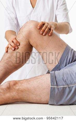 Close-up of physiotherapist treating knee after injury poster