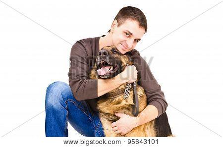 Happy young man hugging a German shepherd