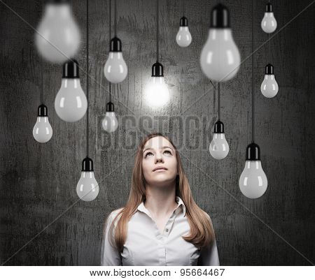 Charming Lady Is Looking Upward At The Hanging Light Bulbs. A Concept Of Searching New Ideas. Dark C