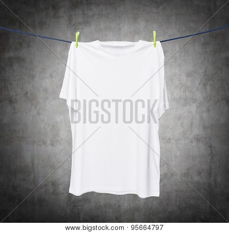 Close Up Of A White T-shirt On The Rope. Concrete Background.