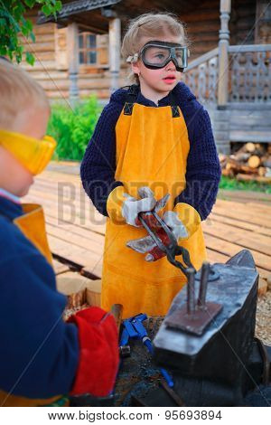 Brother and sister stand near anvil, tongs sister holding blank horseshoes, looking away