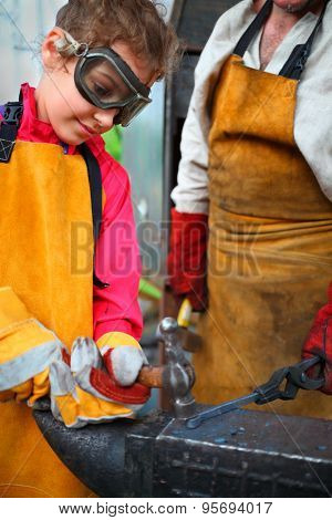 Girl in goggles and yellow apron with  hammer hitting anvil in smithy