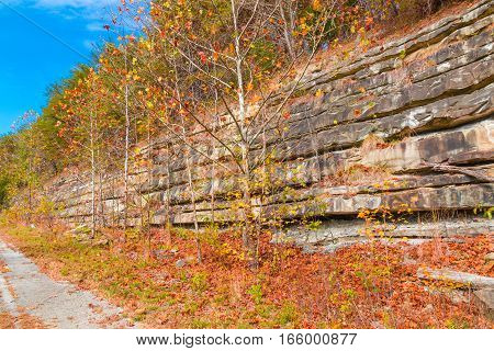 Mountain cliff with rock layers colorful stone formations of rocks stacked over the hundreds of years. Autumn season.