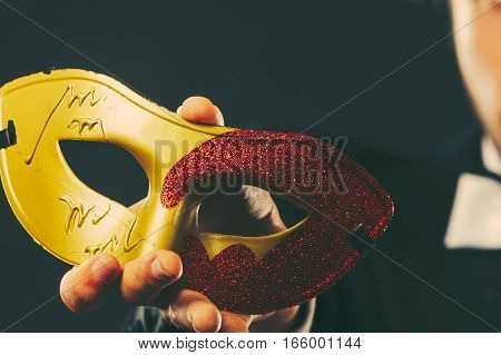 Holidays people and celebration concept. Male hand holding red golden carnival mask closeup on dark