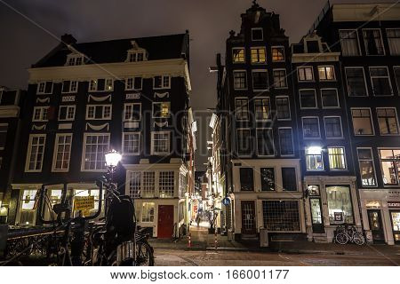 AMSTERDAM NETHERLANDS - JANUARY 10 2017: Famous vintage buildings of Amsterdam city at night time. General landscape view at tradition Dutch arcitecture. January 10 2017 - Amsterdam - Netherlands.