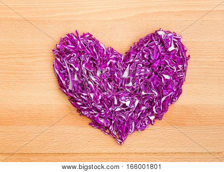 Chopped red cabbage in heart shape on wooden cutting board.