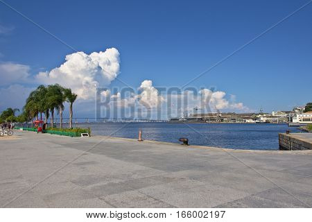 Guanabara bay seen from Praca Maua with palm trees awesome clouds and the Rio-Niteroi bridge in the background.
