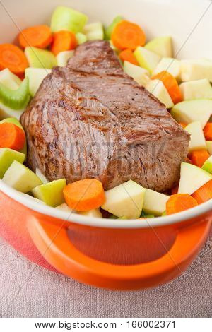Beef Roast prepared with carrots apples and celery in french oven. selective focus shallow dof
