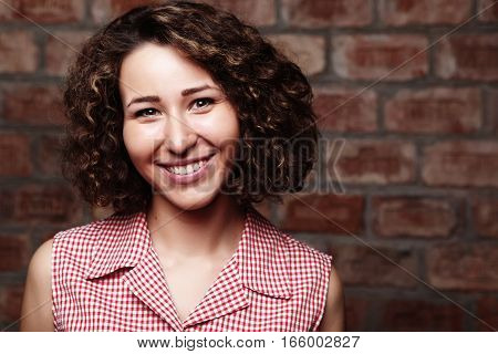 Cheerful and attractive curly woman on brick wall