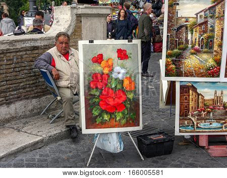 Rome, October 23 2010: A man is selling paintings by the Spanish Steps.