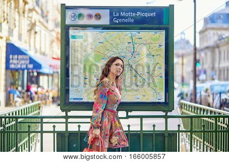 Young Parisian Woman Near The Subway Plan, Looking For The Direction