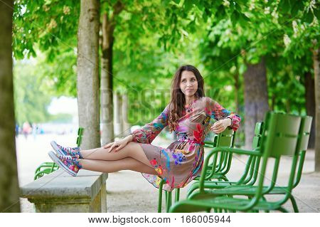 Parisian Woman Relaxing In The Tuileries Garden On A Sunny Summer Day