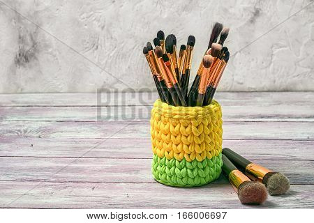 yellow and green knitted basket with brushes for make-up copy space.