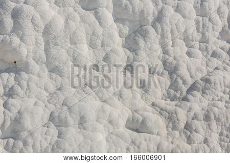 White limestone texture that was layered with the water on the open pit.