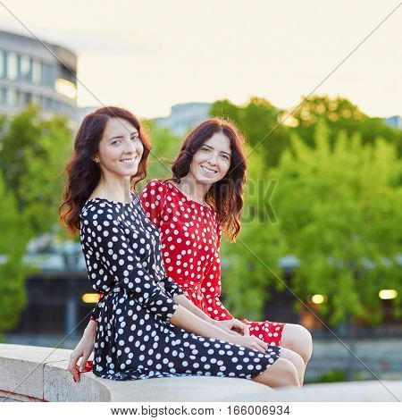 Beautiful Twin Sisters In Red And Black Polka Dot Dresses