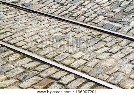 Railroad tracks cross through an old stone street in Savannah Georgia.