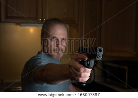 Man with handgun in kitchen Gun in focus only trigger finger in the register position