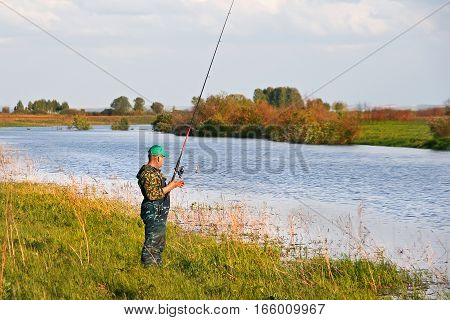 The river Inya cherepanovsky district Novosibirsk oblast Siberia Russia - may 24 2007: a fisherman with a spinning rod catches of predatory fish