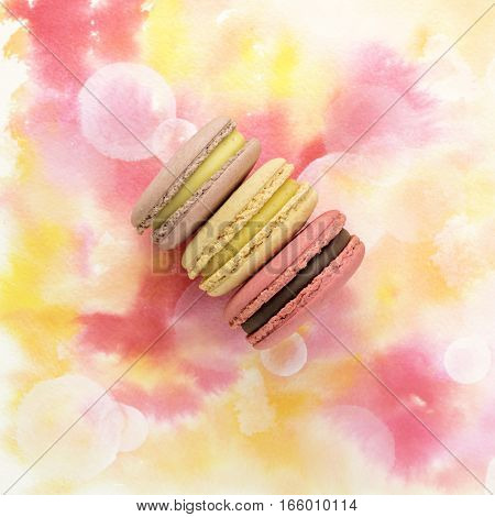 A photo of tender pastel macarons, shot from above on a pink watercolor texture, with copyspace