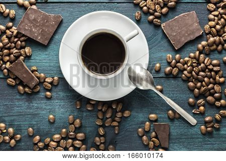 A cup of black coffee, shot from above on a wooden boards texture, with beans scattered around, and chocolate pieces. A horizontal design template for a cafe or shop. Selective focus