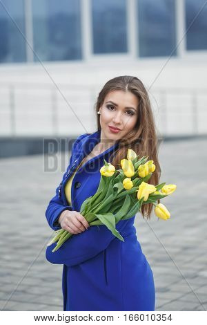 Young attractive girl in a blue coat and yellow dress holding a bouquet of yellow tulips. Spring is coming to town. She looks into the camera