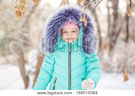 Pretty little girl in winter park. She smiles. Outdoor Activities. Close-up portrait