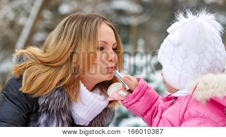 Daughter mother paints her lips hygienic lipstick. Facial Skin Care. Family walk in a winter park.