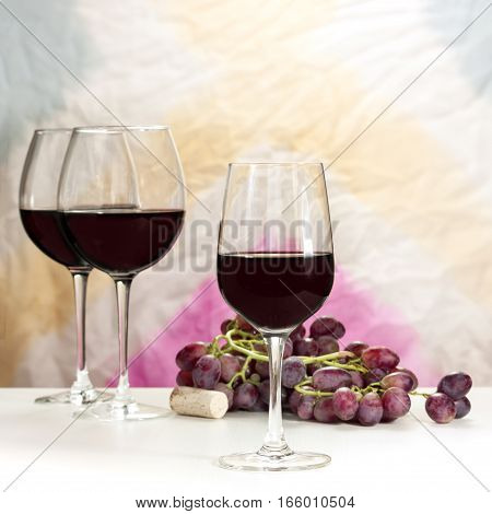 Photo of a glass of red wine, with more blurred glasses in the background, and also out of focus grapes and cork