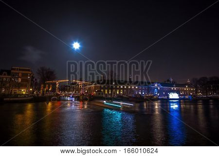 AMSTERDAM NETHERLANDS - JANUARY 12 2017: Cruise boats rush in night canals. Light installations on night canals of Amsterdam within Light Festival at full moon. Amsterdam - Netherland.