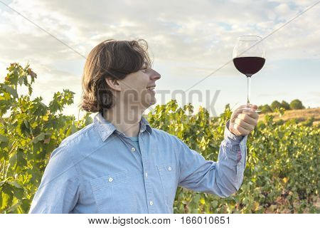 A photo of a happy winemaker, tasting his wine in a vineyard