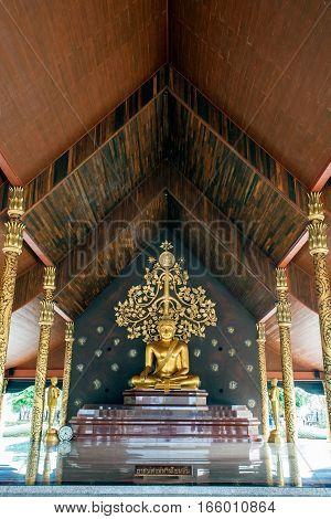 UBON RATCHATHANI, THAILAND-JANUARY 16, 2017 : Golden sitting Buddha in Wat Sirindhorn Wararam Phu Prao temple boasts the main hall with nice artwork that is illuminated at dusk. The main artwork is a ceramic tiles wall