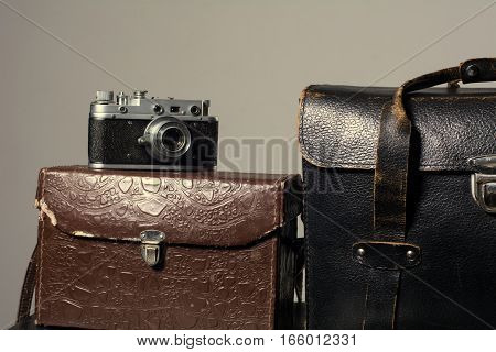 Close-up Of A Stack Vintage Shabby Suitcases And Camera