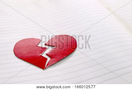 Broken paper heart on notebook page with copy space / Valentine concept