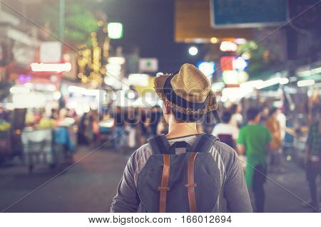 Young Asian traveling backpacker in Khaosan Road night market in evening in Bangkok Thailand