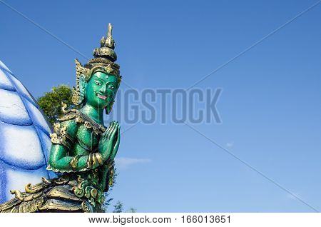 Thai Tradition Green Male Angel Sawasdee (Hello) with Blue Sky at Wat Rong Sua Ten Chiang Rai Thailand. Most Visited from Tourist.
