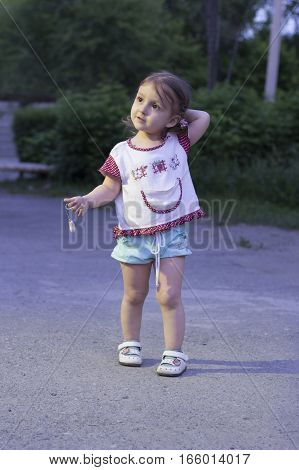 Little girl lost. The child was left alone at night on the street in the park and think which way to go