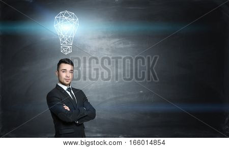 Businessman on black chalkboard background with a glowing gridshell bulb above him. Business and success. Inspirational ideas. Innovation.