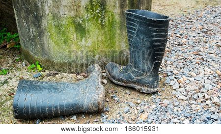 Dirty boots on the ground. Boots for the flood. abstract of difficulty
