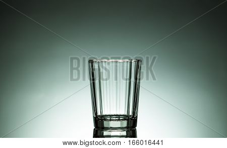 Small empty cup green background,small glass for drink