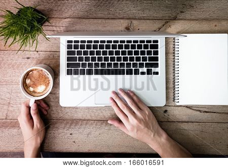 Man Using Laptop And Coffee Cup Notepad On Wood Table