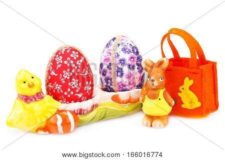 Easter decoration with colorful eggs in ceramic setting bunny and bag isolated on white background.