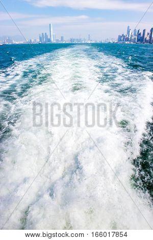waves behing a passenger cruise leaving Hong Kong China