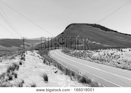 Mountain road valley entry in vintage black and white landscape contrasts.