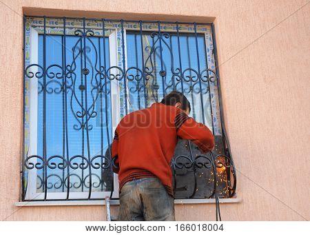 KIEV UKRAINE - JANUARY 23 2017: Welding on window iron security bars. Contractor installing window iron security bars with weld.