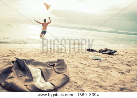 businessman running into the sea, happy to finally be out of the office