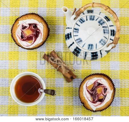 Tea In Cup, Two Cakes, Cinnamon Sticks And Teapot